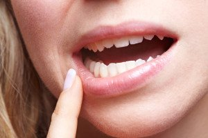 Woman with pain in her gums holding finger to mouth